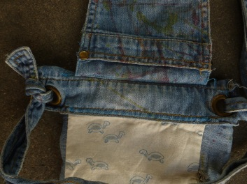 This is the top of the bookbag. It is visible that the original fastening method of the dungarees is kept to attach the straps to the bag.